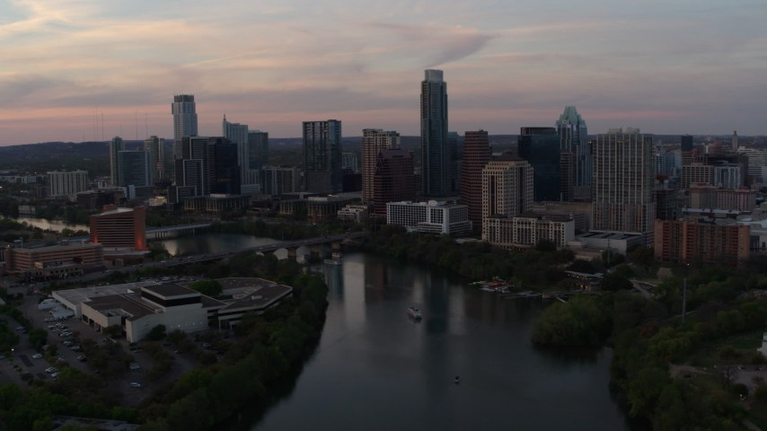 5.7K stock footage aerial video of flying away from the skyline from over Lady Bird Lake at sunset in Downtown Austin, Texas Aerial Stock Footage | DX0002_110_019