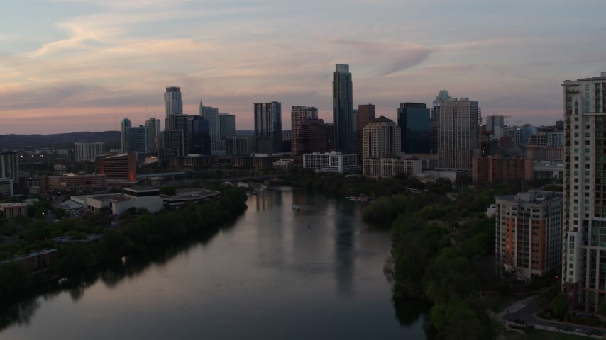 5.7K stock footage aerial video focus on the skyline, descend toward Lady Bird Lake at sunset in Downtown Austin, Texas Aerial Stock Footage | DX0002_110_020