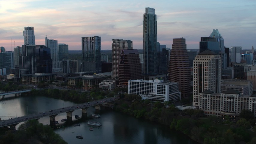 5.7K stock footage aerial video of a reverse view of Austonian and skyline from Lady Bird Lake at twilight in Downtown Austin, Texas Aerial Stock Footage | DX0002_110_023