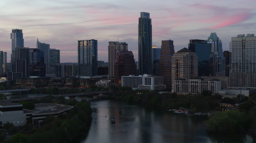 5.7K aerial video a stationary view of city skyline by Lady Bird Lake at twilight in Downtown Austin, Texas Aerial Stock Footage | DX0002_110_027