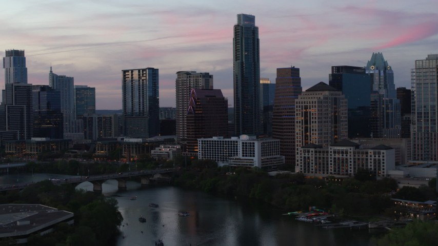 5.7K stock footage aerial video focus on The Austonian in city skyline during allow approach from Lady Bird Lake at twilight in Downtown Austin, Texas Aerial Stock Footage | DX0002_110_028