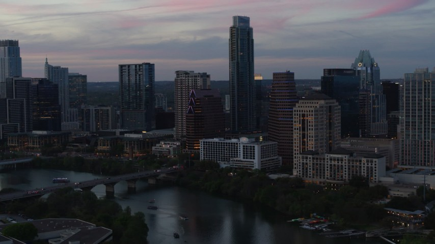 5.7K aerial video reverse view of The Austonian and city skyline beside Lady Bird Lake at twilight in Downtown Austin, Texas Aerial Stock Footage | DX0002_110_029