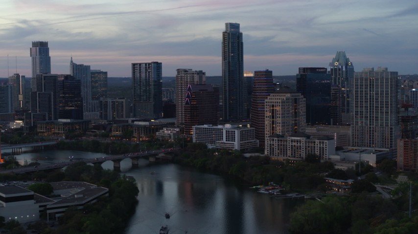 5.7K stock footage aerial video of The Austonian and city skyline seen from Lady Bird Lake at twilight in Downtown Austin, Texas Aerial Stock Footage | DX0002_110_031