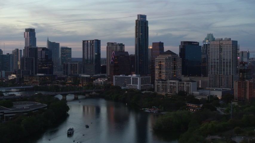 5.7K aerial video of The Austonian at the center of city skyline seen from Lady Bird Lake at twilight in Downtown Austin, Texas Aerial Stock Footage | DX0002_110_032