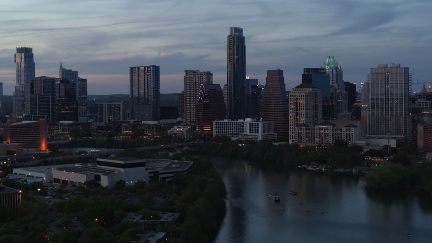 5.7K stock footage aerial video of The Austonian and city skyline seen while passing over Lady Bird Lake at twilight in Downtown Austin, Texas Aerial Stock Footage | DX0002_110_033