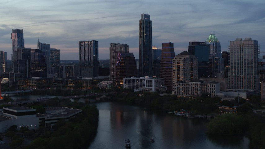 5.7K stock footage aerial video of tall Austonian and city skyline seen during pass over Lady Bird Lake at twilight in Downtown Austin, Texas Aerial Stock Footage | DX0002_110_034