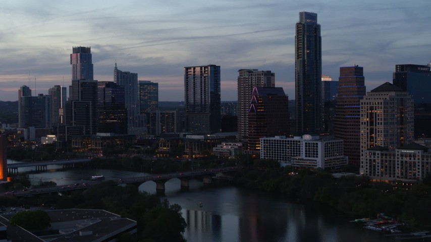 5.7K stock footage aerial video approach bridge and city skyline from Lady Bird Lake at twilight in Downtown Austin, Texas Aerial Stock Footage | DX0002_110_035