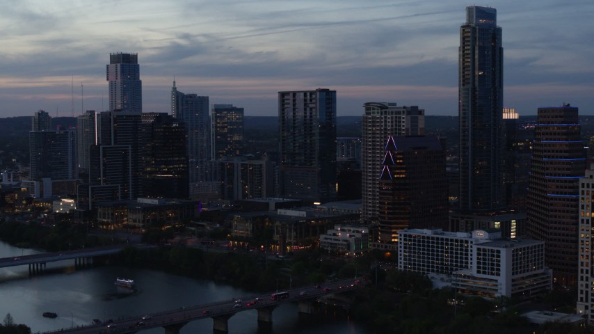 5.7K stock footage aerial video reverse view of skyscrapers by Lady Bird Lake and bridge at twilight in Downtown Austin, Texas Aerial Stock Footage | DX0002_110_037