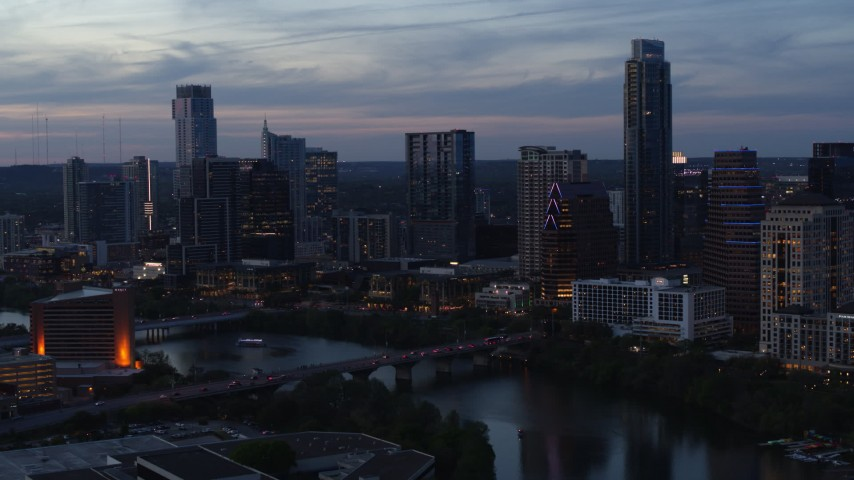 5.7K stock footage aerial video fly away from the skyline by Lady Bird Lake and bridge at twilight in Downtown Austin, Texas Aerial Stock Footage | DX0002_110_038