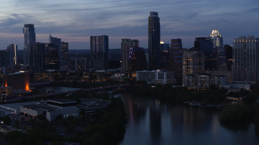 5.7K aerial video pan across skyline by Lady Bird Lake and bridge at twilight in Downtown Austin, Texas Aerial Stock Footage | DX0002_110_039