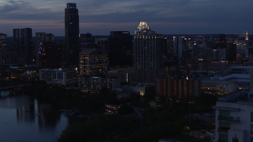 5.7K stock footage aerial video of San Jacinto Center seen from Lady Bird Lake at twilight in Downtown Austin, Texas Aerial Stock Footage | DX0002_110_043