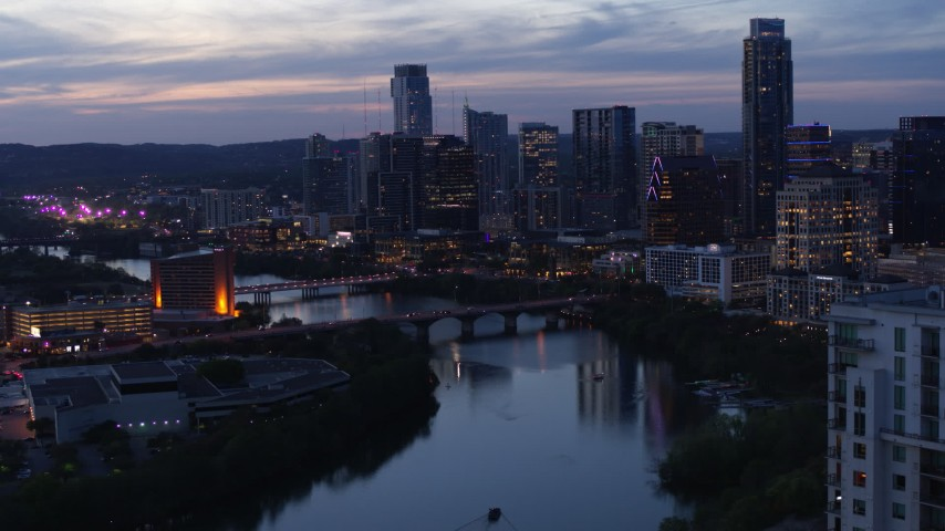 5.7K aerial video reverse view of Congress Avenue Bridge, Lady Bird Lake, skyline at twilight in Downtown Austin, Texas Aerial Stock Footage DX0002_110_044