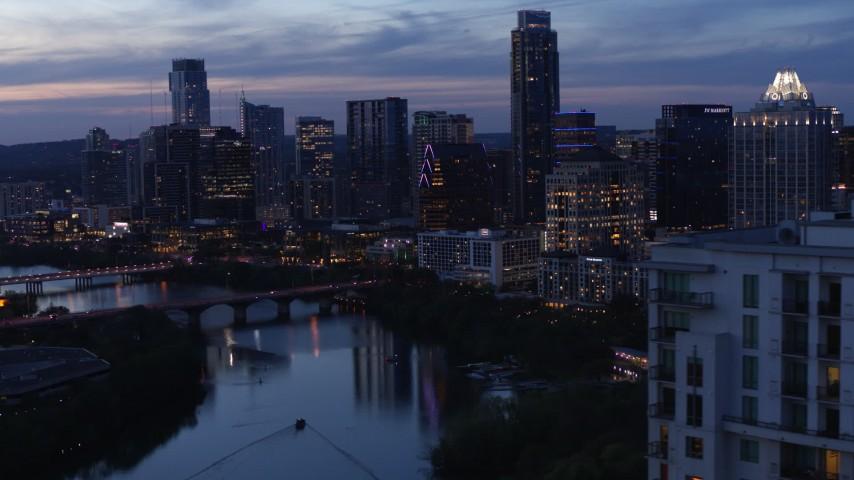 5.7K stock footage aerial video pass over Lady Bird Lake, focus on Congress Avenue Bridge and skyline at twilight in Downtown Austin, Texas Aerial Stock Footage | DX0002_110_047