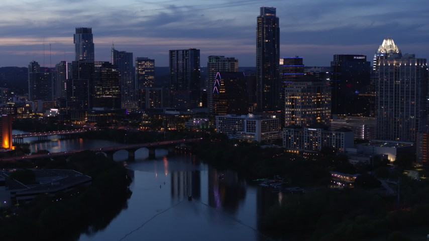 5.7K aerial video reveal Lady Bird Lake and Congress Avenue Bridge, focus on skyline at twilight in Downtown Austin, Texas Aerial Stock Footage | DX0002_110_048