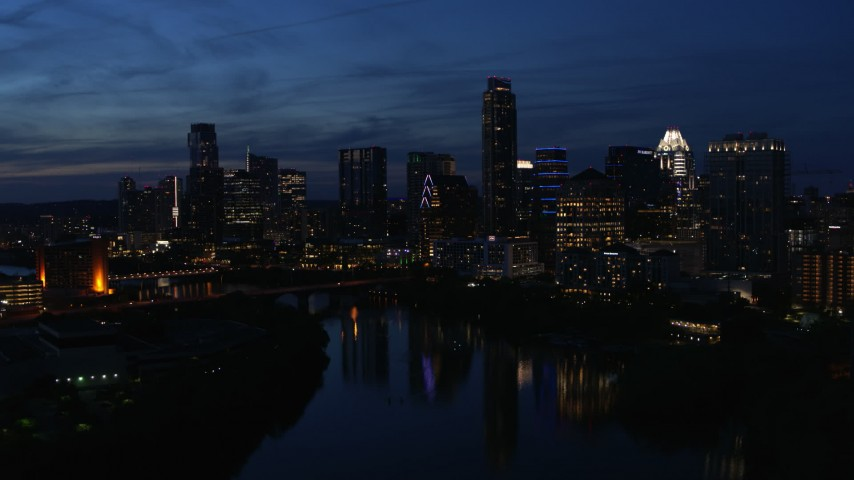 5.7K stock footage aerial video follow Lady Bird Lake, focus on the waterfront skyline at twilight in Downtown Austin, Texas Aerial Stock Footage | DX0002_111_002
