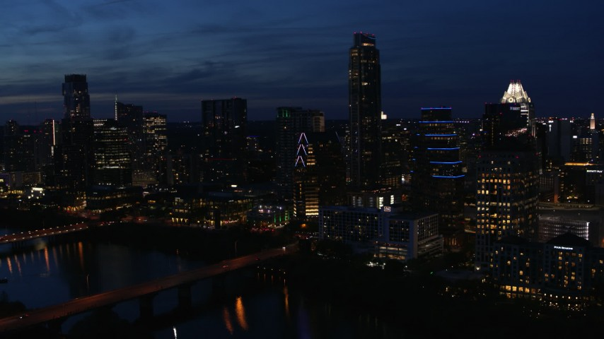 5.7K aerial video approach Austonian and waterfront skyline from Lady Bird Lake at twilight in Downtown Austin, Texas Aerial Stock Footage | DX0002_111_003