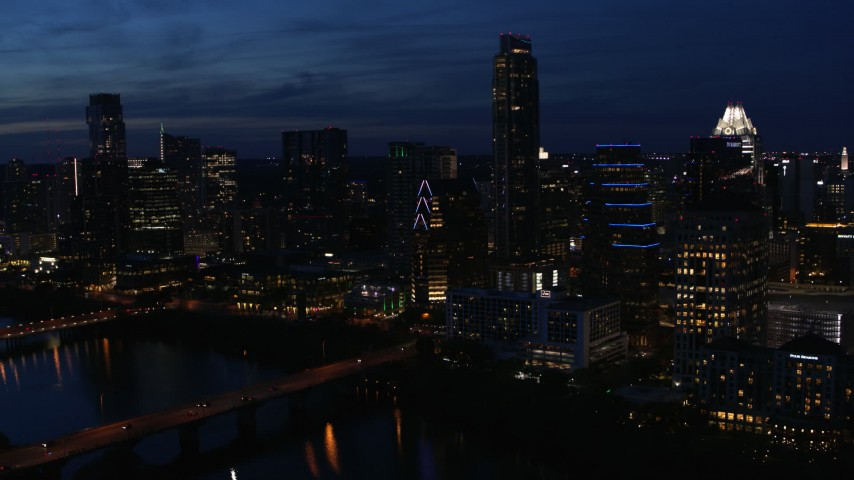 5.7K aerial video fly away from Austonian and waterfront skyline, seen from Lady Bird Lake at twilight in Downtown Austin, Texas Aerial Stock Footage | DX0002_111_004