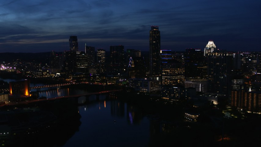 5.7K aerial video a reverse view of waterfront skyline, seen from Lady Bird Lake at twilight in Downtown Austin, Texas Aerial Stock Footage | DX0002_111_005