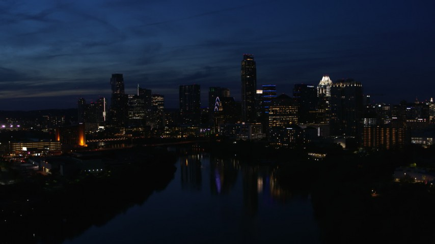 5.7K aerial video slowly flyby waterfront skyline on the shore of Lady Bird Lake at twilight in Downtown Austin, Texas Aerial Stock Footage | DX0002_111_008