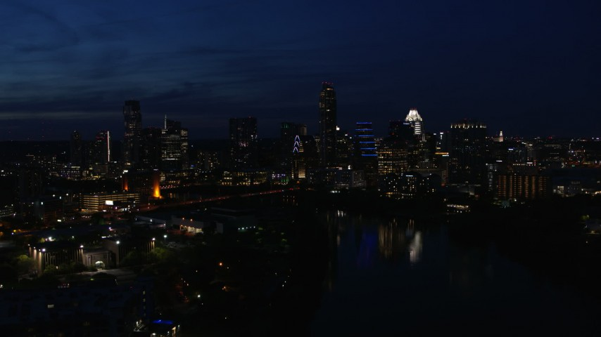 5.7K aerial video ascend and flyby waterfront skyline on the shore of Lady Bird Lake at twilight in Downtown Austin, Texas Aerial Stock Footage | DX0002_111_010
