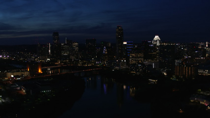 5.7K stock footage aerial video passing by waterfront skyline on the shore of Lady Bird Lake at twilight in Downtown Austin, Texas Aerial Stock Footage | DX0002_111_011