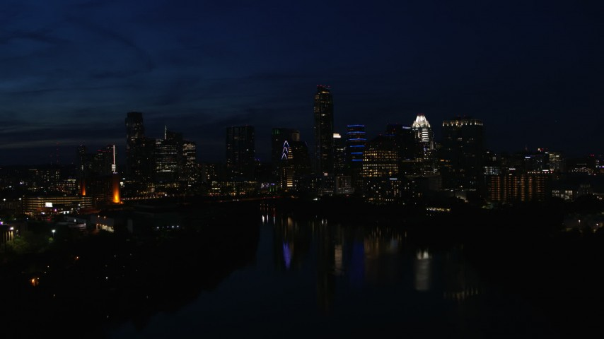 5.7K aerial video slowly flyby city's waterfront skyline on the opposite shore of Lady Bird Lake at night in Downtown Austin, Texas Aerial Stock Footage | DX0002_111_013
