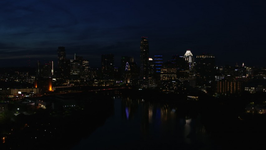 5.7K aerial video of city's waterfront skyline on the opposite shore of Lady Bird Lake during descent at night in Downtown Austin, Texas Aerial Stock Footage | DX0002_111_015