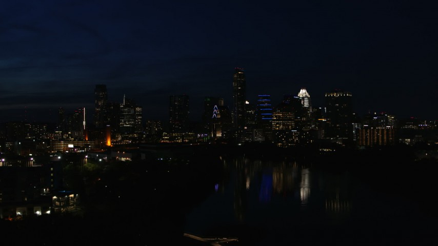 5.7K stock footage aerial video descend and focus on waterfront skyline on the opposite shore of Lady Bird Lake at night in Downtown Austin, Texas Aerial Stock Footage | DX0002_111_018