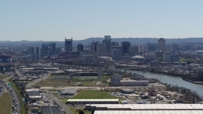 5.7K stock footage aerial video a wide view of the city's skyline and river seen from warehouse buildings in Downtown Nashville, Tennessee Aerial Stock Footage | DX0002_112_015