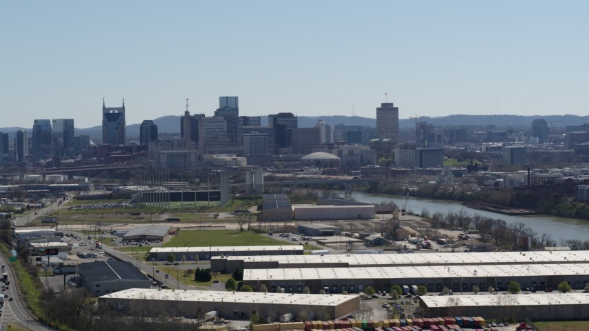 5.7K stock footage aerial video a wide view of the city's skyline and river seen while passing warehouse buildings in Downtown Nashville, Tennessee Aerial Stock Footage | DX0002_112_018