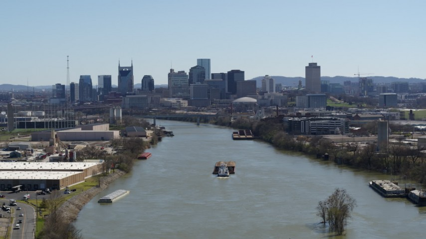 5.7K stock footage aerial video a barge sailing the river toward the city's skyline, Downtown Nashville, Tennessee Aerial Stock Footage | DX0002_112_021