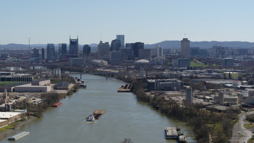 5.7K stock footage aerial video flying by barge sailing the river toward the city's skyline, Downtown Nashville, Tennessee Aerial Stock Footage | DX0002_112_022