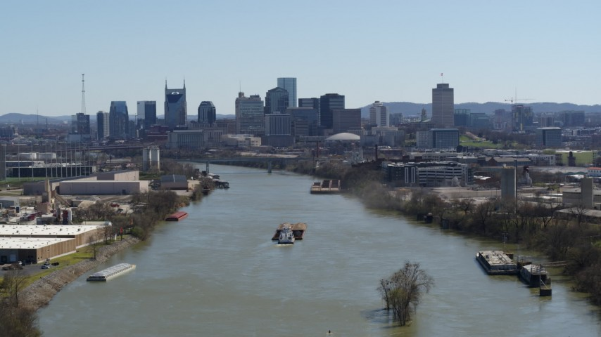 5.7K stock footage aerial video passing by barge on the river toward the city's skyline, Downtown Nashville, Tennessee Aerial Stock Footage | DX0002_112_023