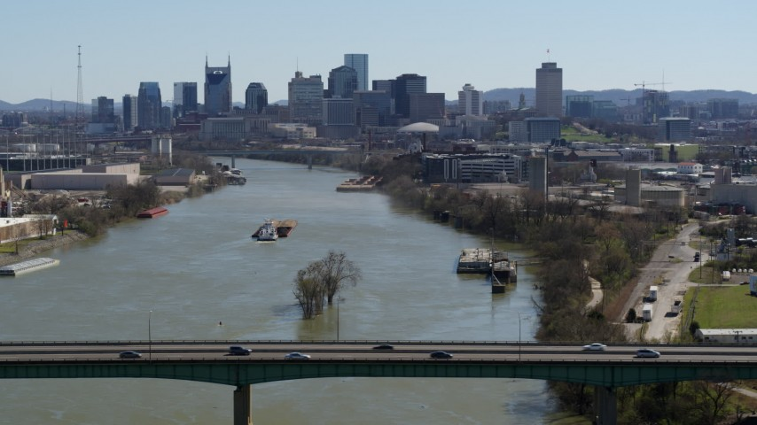 5.7K stock footage aerial video a barge sailing the river toward the city's skyline, seen from a bridge, Downtown Nashville, Tennessee Aerial Stock Footage | DX0002_112_024