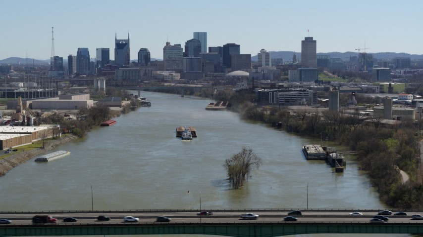 5.7K stock footage aerial video a barge on the river, sailing toward the city's skyline, seen from a bridge, Downtown Nashville, Tennessee Aerial Stock Footage | DX0002_112_025