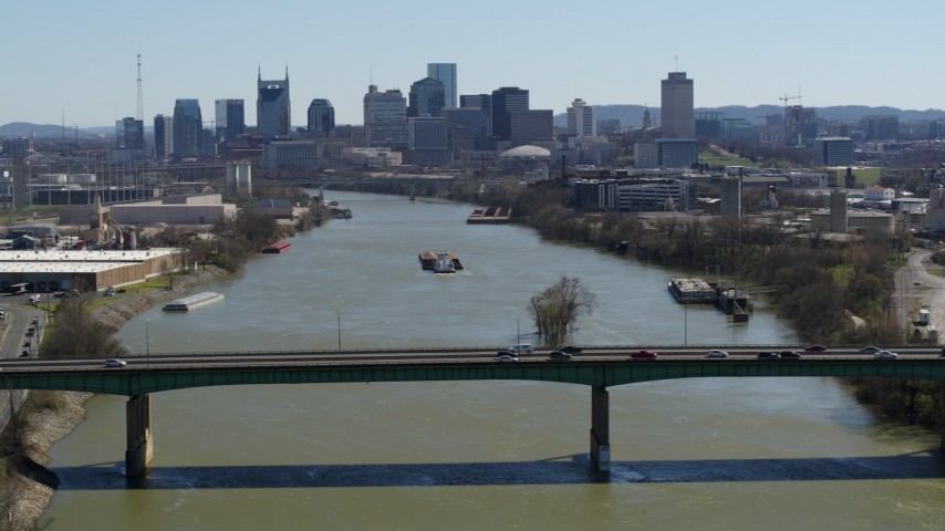 5.7K stock footage aerial video a barge on the river, sailing toward the city's skyline, seen seen while flying by bridge, Downtown Nashville, Tennessee Aerial Stock Footage | DX0002_112_026