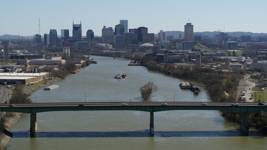 5.7K stock footage aerial video passing a bridge with view of barge sailing toward the city's skyline, Downtown Nashville, Tennessee Aerial Stock Footage | DX0002_112_028