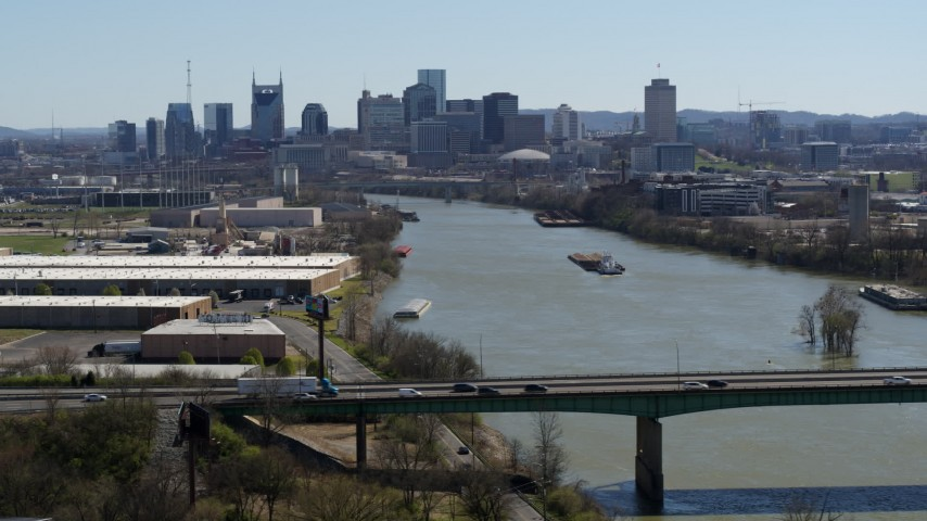 5.7K stock footage aerial video a highway bridge, with view of barge sailing toward city's skyline, Downtown Nashville, Tennessee Aerial Stock Footage | DX0002_112_029
