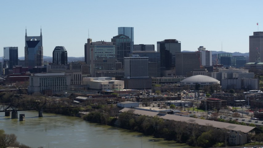 5.7K stock footage aerial video of crossing the river, focus on the city's skyline, Downtown Nashville, Tennessee Aerial Stock Footage | DX0002_112_033