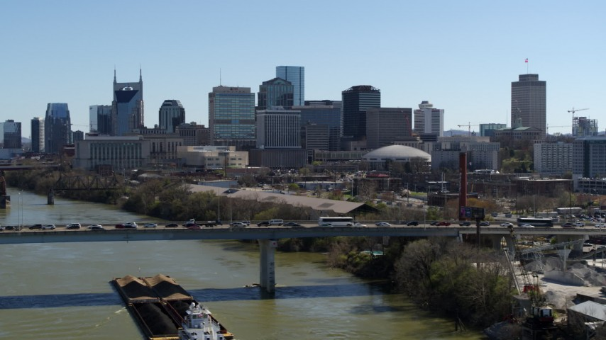 5.7K stock footage aerial video of flying by city's skyline, reveal heavy traffic on bridge over the river, Downtown Nashville, Tennessee Aerial Stock Footage | DX0002_113_001