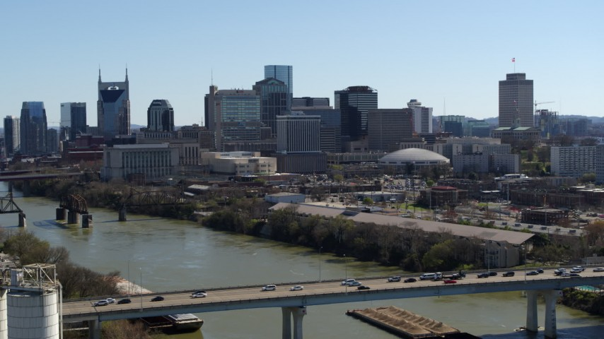 5.7K stock footage aerial video ascend by heavy traffic on bridge over the river, focus on skyline, Downtown Nashville, Tennessee Aerial Stock Footage | DX0002_113_002