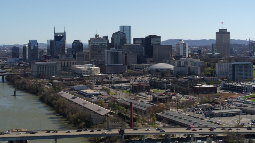 5.7K stock footage aerial video the city skyline seen from bridge spanning the river, Downtown Nashville, Tennessee Aerial Stock Footage | DX0002_113_004