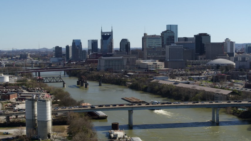 5.7K stock footage aerial video focus on city skyline, reveal traffic on bridge spanning the river, Downtown Nashville, Tennessee Aerial Stock Footage | DX0002_113_005