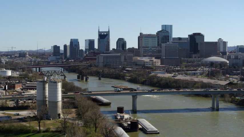 5.7K stock footage aerial video focus on city skyline while passing traffic on bridge over the river, Downtown Nashville, Tennessee Aerial Stock Footage DX0002_113_006 | Axiom Images