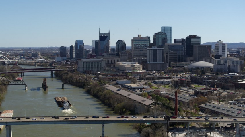 5.7K stock footage aerial video the city skyline while flying by traffic on bridge over the river, Downtown Nashville, Tennessee Aerial Stock Footage | DX0002_113_007