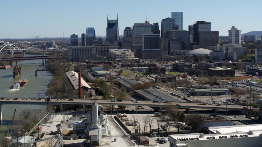 5.7K stock footage aerial video a view of city's skyline while flying away from traffic on bridge over the river, Downtown Nashville, Tennessee Aerial Stock Footage | DX0002_113_008