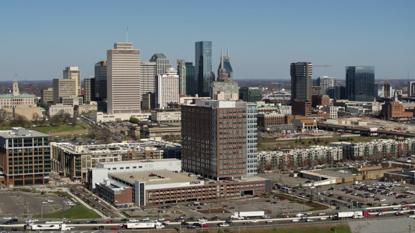 5.7K stock footage aerial video descend by office building for view of city's skyline behind apartment buildings in Downtown Nashville, Tennessee Aerial Stock Footage | DX0002_113_019