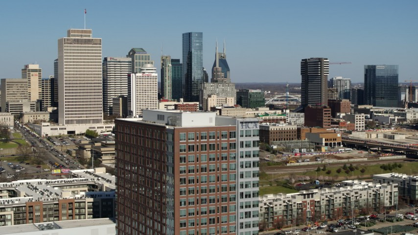 5.7K stock footage aerial video descend by office building, skyline in background, Downtown Nashville, Tennessee Aerial Stock Footage | DX0002_113_023