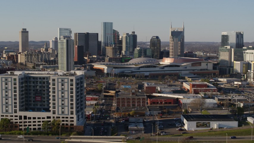 5.7K stock footage aerial video fly away from the city skyline behind the convention center, descend by apartments in Downtown Nashville, Tennessee Aerial Stock Footage | DX0002_114_022