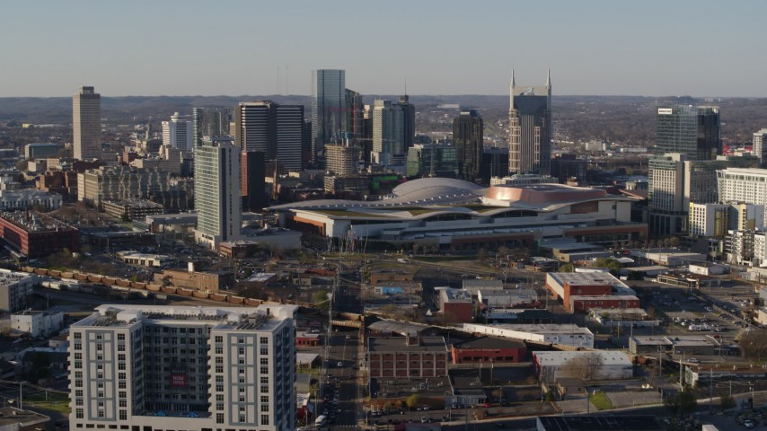 5.7K stock footage aerial video of flying away from the city skyline behind the convention center in Downtown Nashville, Tennessee Aerial Stock Footage | DX0002_114_024